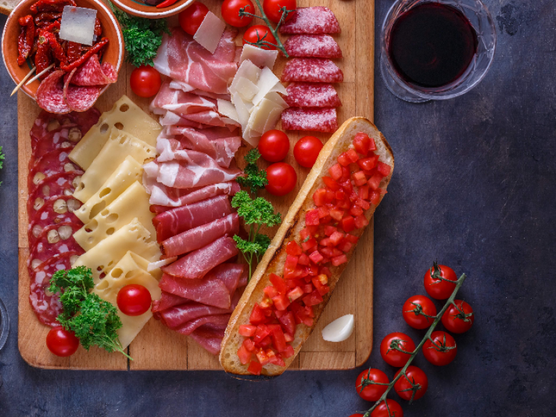 Board of cured meat, cheese and bread with wine, copyspace.